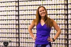 Jenna Bee, posing in front of Deliciousness in Cans.
