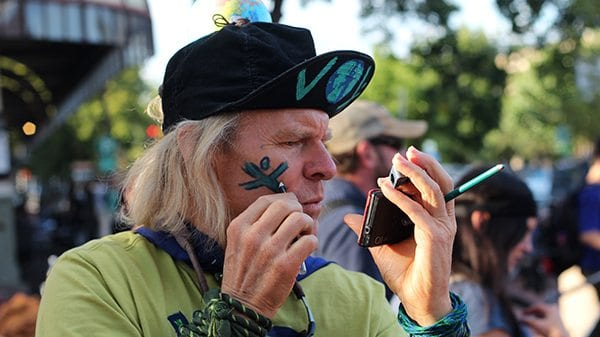 "EARTH MAN uses the reflection of his phone screen to put the Team Earth symbols on his face. He said, ""If we're going to win this thing we need to start representing Team Earth just like we do for our other teams we support."""