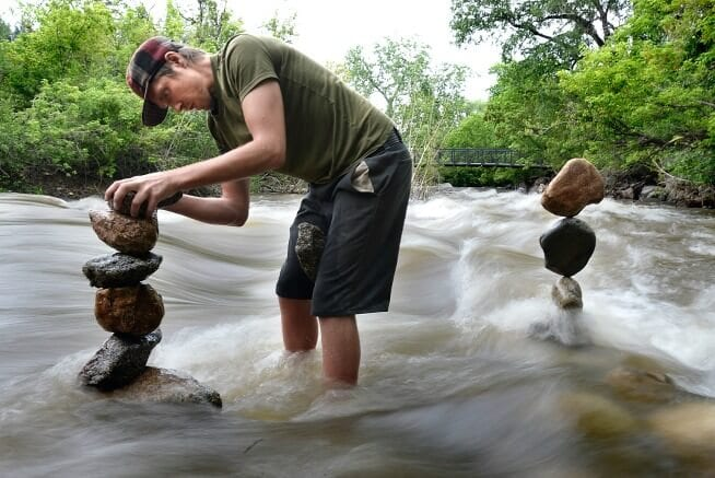 Michael Grab aka Gravity Glue balancing rocks in the Boulder Creek. Photo Credit: Jeremy Papasso/Daily Camera.