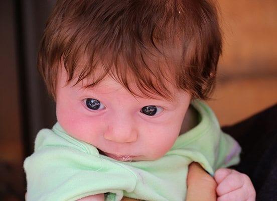 A newborn baby's eyes shine on Pearl Street.