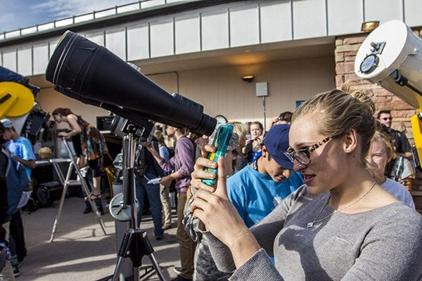 A lot of people took pictures with their phones through the binoculars and telescopes to capture the eclipse. (Photo: Joseph Wirth)