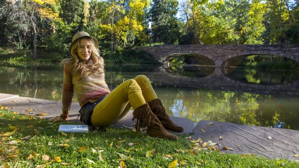 Local filmmaker and CU student Susan Sebanc reads her book and stretches out by the Varsity Lake. (Photo: Joseph Wirth)