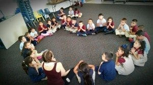 Kids gather in a heart-shaped circle to learn about the principles of yoga.