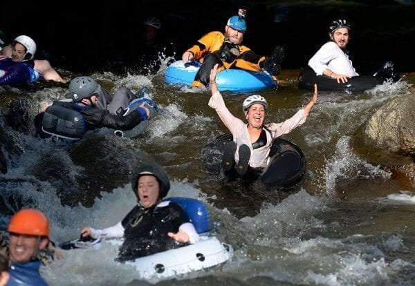 """BOULDER, CO - JULY 14: Employees from Boulder's LogRhythm Inc. and others, don their professional attire and jump in to Boulder Creek on inner tubes and float to work on the company's """"Tube to Work Day"""". (Photo by Kathryn Scott Osler/The Denver Post via Getty Images)"""