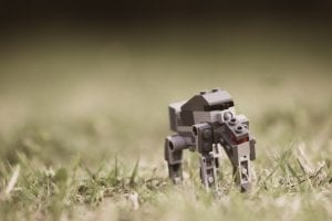 tilt photography of gray robot on green grass at daytime