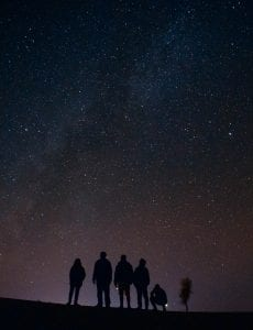 silhouette of five persons staring at the stars at nigh
