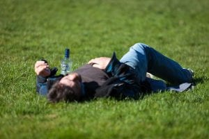 man lying on the ground with a bottle next to him
