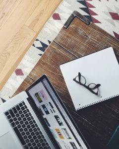 turned on MacBook Pro near black framed eyeglasses